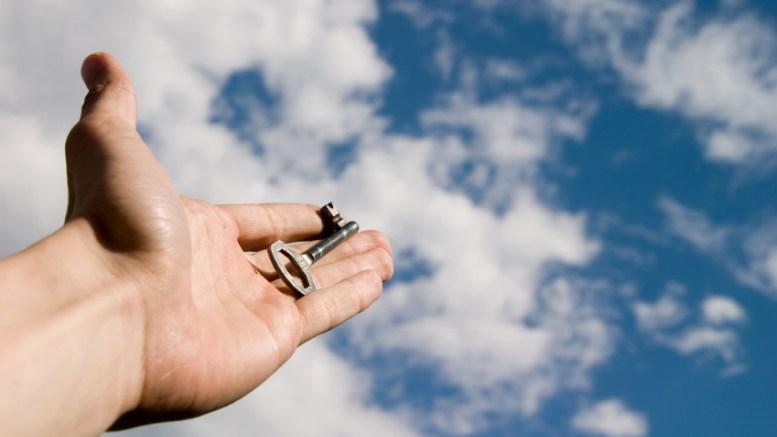 Hand holding a key against a blue sky
